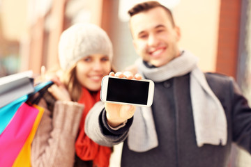 Happy couple showing smartphone while shopping