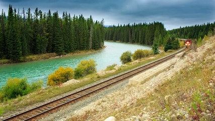 A short train traveling along a mountain Bow river