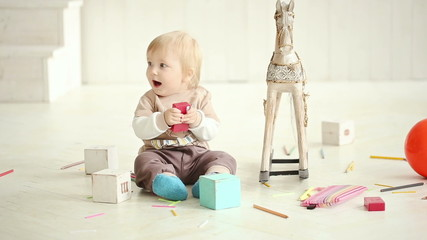 little boy playing on the floor in a bright room - dolly shot