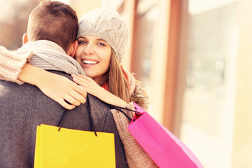 Happy woman hugging a man while shopping