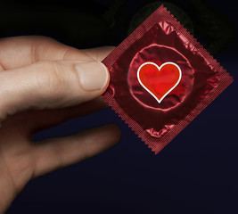 Man's hand with a red condom pack and heart symbol on it