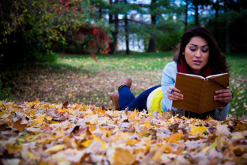 Young woman reading a book lying down on autumn leaves in the fa