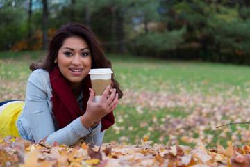 Hispanic woman enjoying a coffee outdoors during autumn