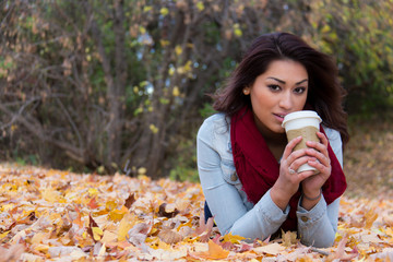 Hispanic woman enjoying a coffee outdoors during fall