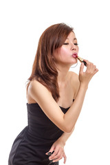 Attractive Asian woman applying lipstick