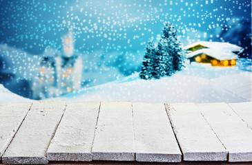 Wooden table against a winter Christmas scene