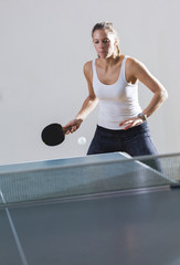 Pretty woman playing table tennis indoors