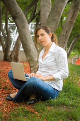 woman in park with her computer