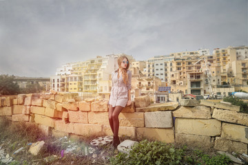 Fashionable girl sitting on a wall in ruins