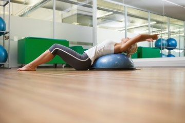Side view of woman stretching her back in fitness studio