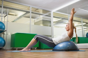 Side view of woman doing fitness exercise in fitness studio