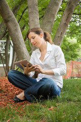 woman in park with mobile tablet