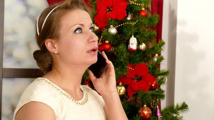Woman speaking by phone on Christmas tree background