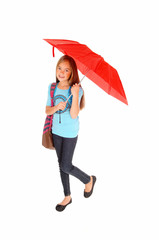 Young girl standing with umbrella.