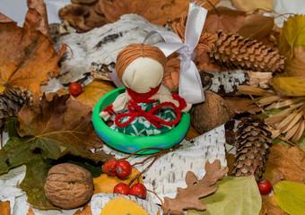 "Autumn background. Traditional Ukrainian ""motanka"" doll-guarded"