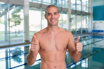 Fit swimmer gesturing thumbs up by pool at leisure center