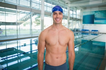 Shirtless fit swimmer by pool at leisure center