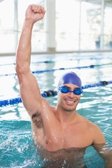 Fit swimmer cheering in pool at leisure center
