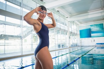 Portrait of female swimmer by pool at leisure center