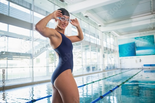 Portrait of female swimmer by pool at leisure center - 73307602