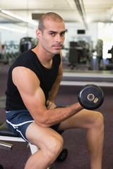 Man exercising with dumbbell in gym