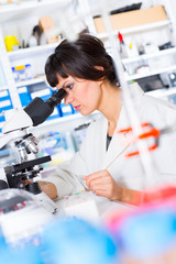 woman in a laboratory looking in a a microscope