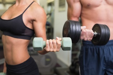 Mid section of couple exercising with dumbbells in gym