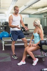 Male trainer talking to fit woman at gym