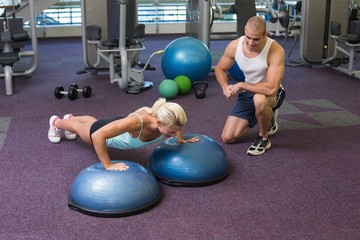 Male trainer assisting woman with push ups at gym