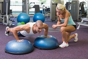 Trainer assisting man with push ups at gym