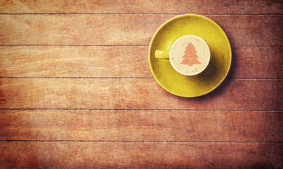 Cappuccino with christmas tree shape on a wooden table.