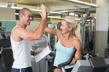 Trainer giving high five to his client on exercise bike at gym
