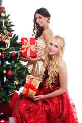 Zwei junge Frauen mit Weihnachtsbaum isoliert