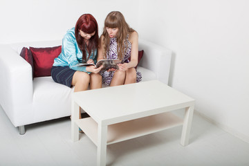 two girls reads magazine