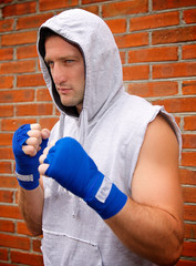 boxer in the hood on the brick wall background