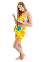 sexy young lass wearing a bright pareo with sunglasses stands