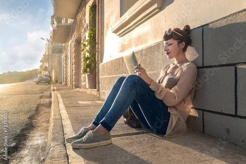 canvas print picture A young girl using a tablet and sitting on the ground
