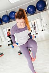 Female Doing Step Aerobics In Gym