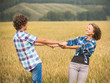 Happy teen boy and girl walking in a rye field