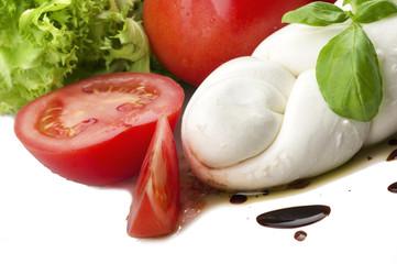 Mozzarella tomatoes and fresh salad on the white