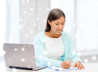 smiling young woman with laptop and notebook