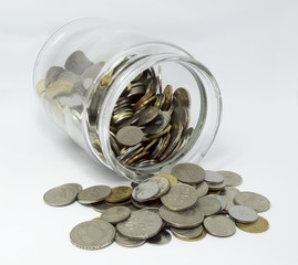 Coins inside glass jar with white background