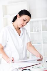 female doctor is writing prescription