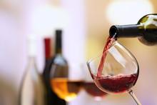 "Постер, картина, фотообои ""Red wine pouring into wine glass, close-up"""