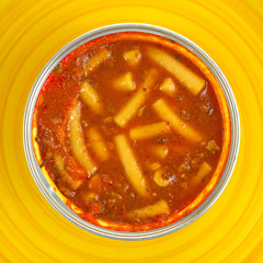 Canned pasta in sauce on a yellow background
