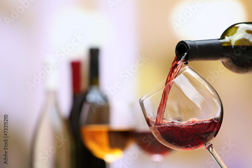 Red wine pouring into wine glass, close-up poster