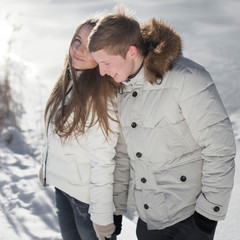 Young couple playing in winter park