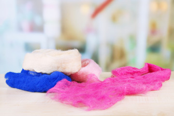 Multicolored wool for felting on table on bright background