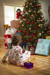 Young girl sitting in front of Christmas tree.
