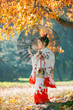 small girl in kimono on the yellow foliage